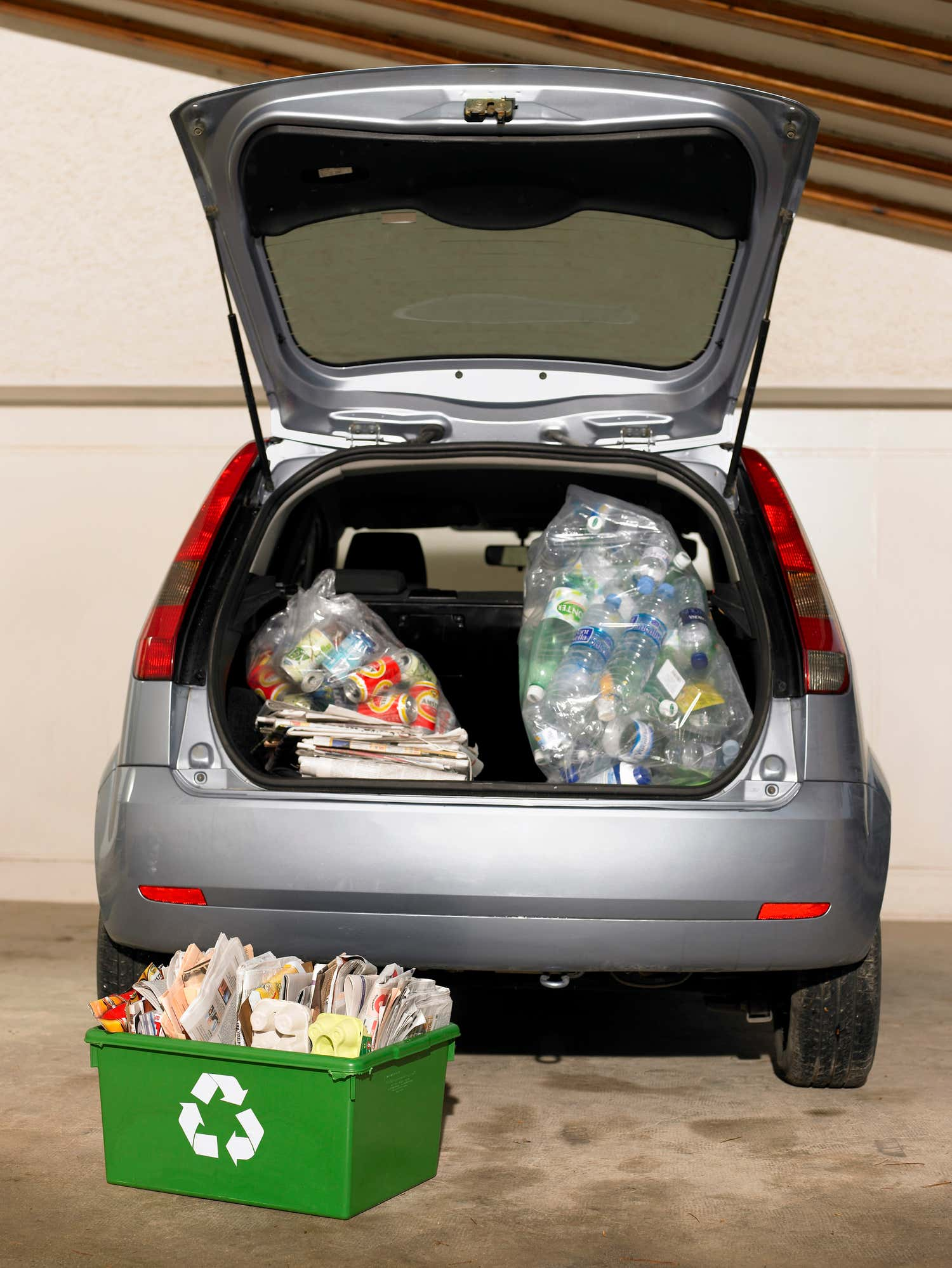 Car trunk open with recycling in it