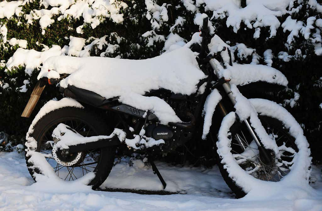 Motorcycle outside in the winter covered in snow