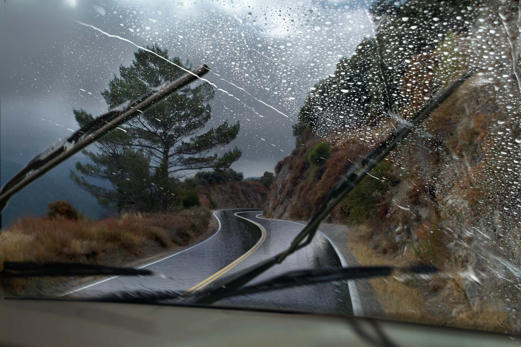 Windshield being cleaned by wiper blades during heavy rain and wind