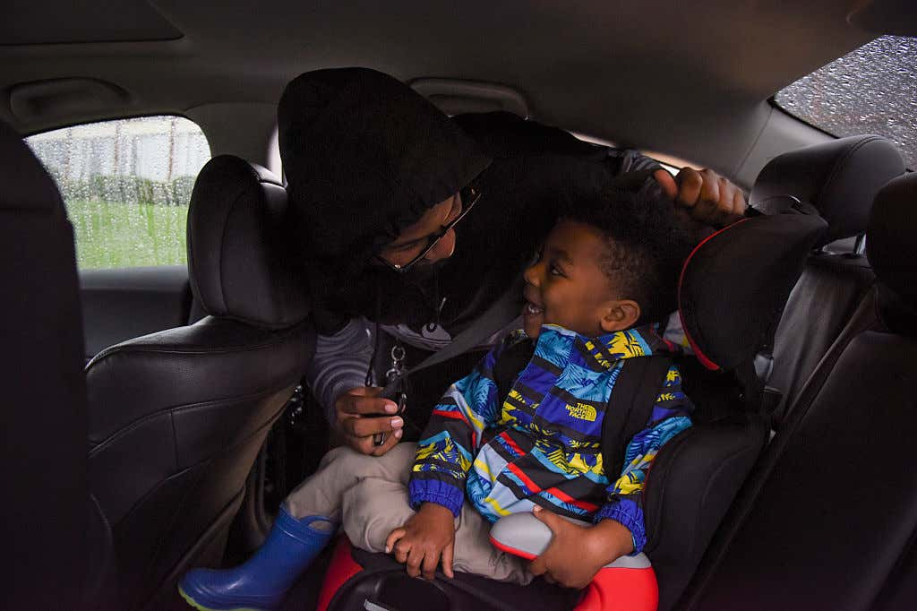 A mom buckles her little boy in his car seat.
