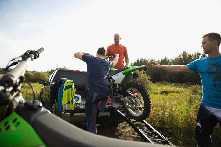 People loading a dirt bike into a truck with a ramp.