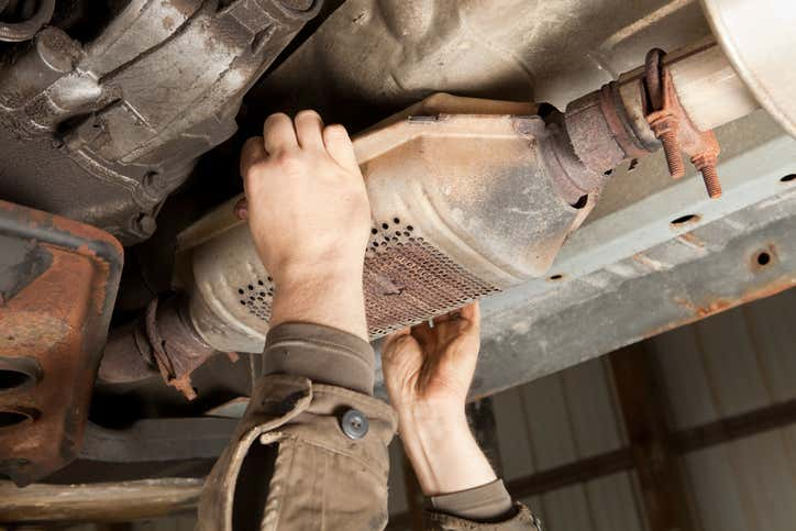 Hands of a mechanic visible in the process of changing an old catalytic converter with rusted parts