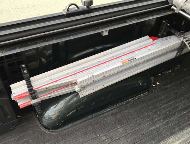 A folded ramp hanging on the side of a truck bed.