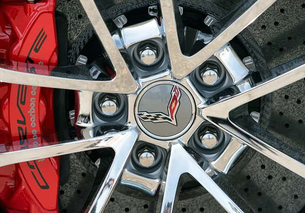 A close-up of a chrome Chevrolet Corvette wheel with red brake calipers.