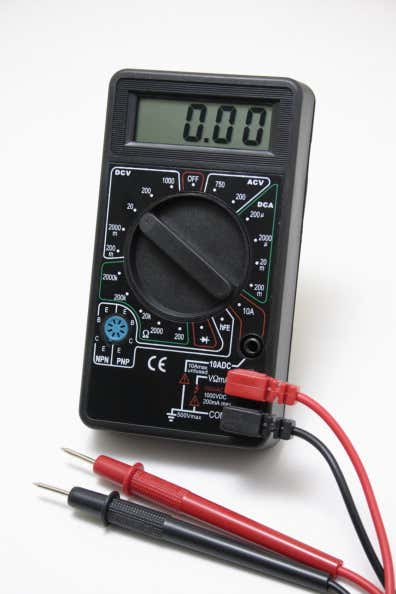 A black automotive multimeter with black and red leads.