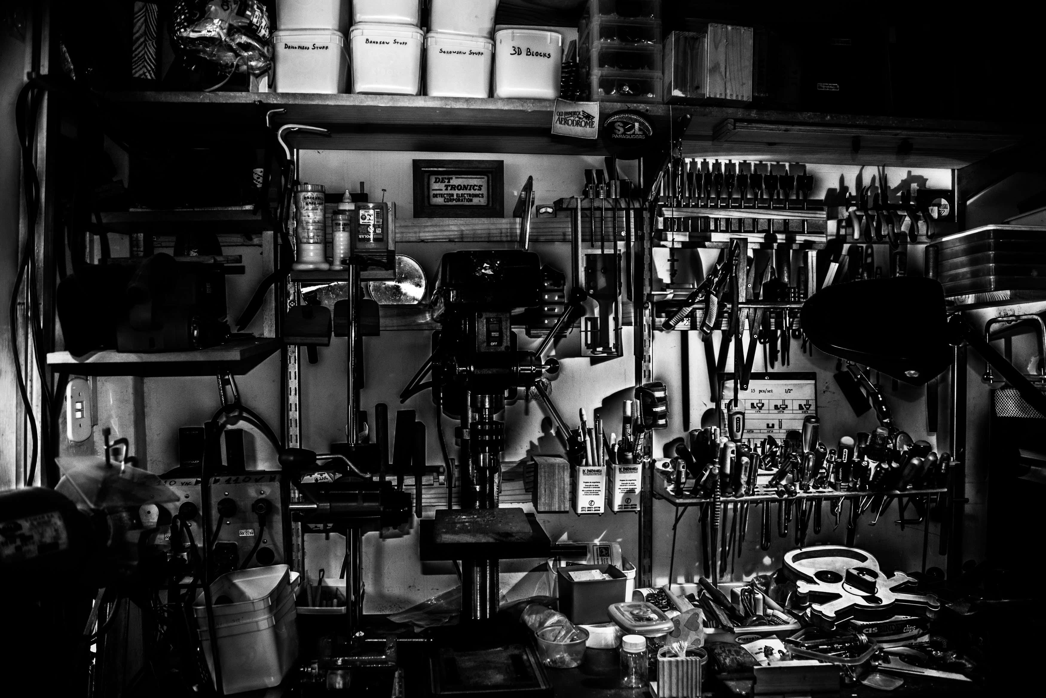 A black and white image showing garage shelving with a variety of tools.