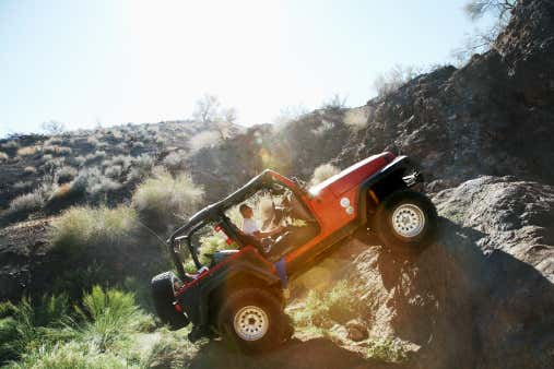 A man drives a red Jeep over a boulder