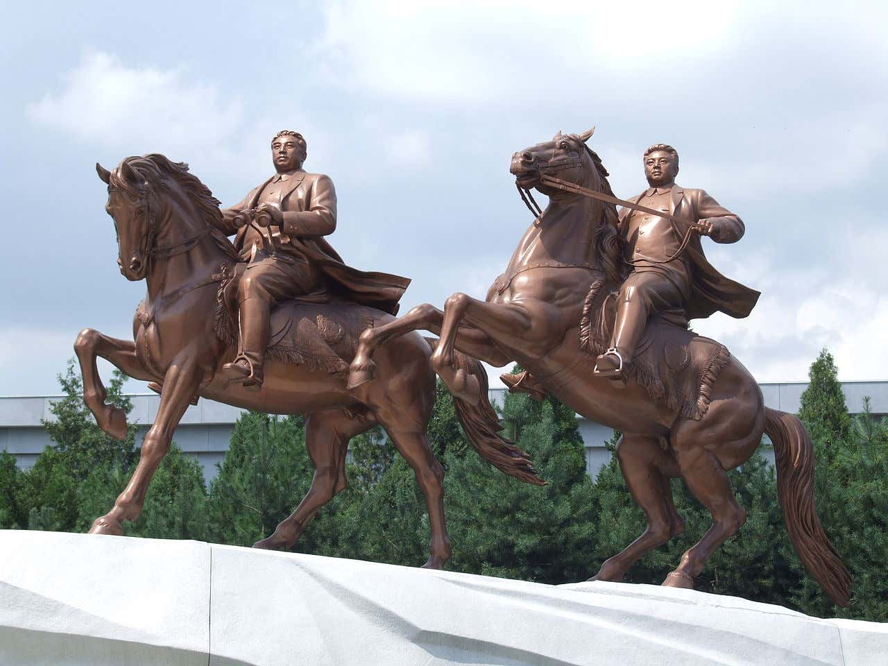 A grand statue located in Pyonyang of Kim Il Sung and Kim Jong Un riding steeds.