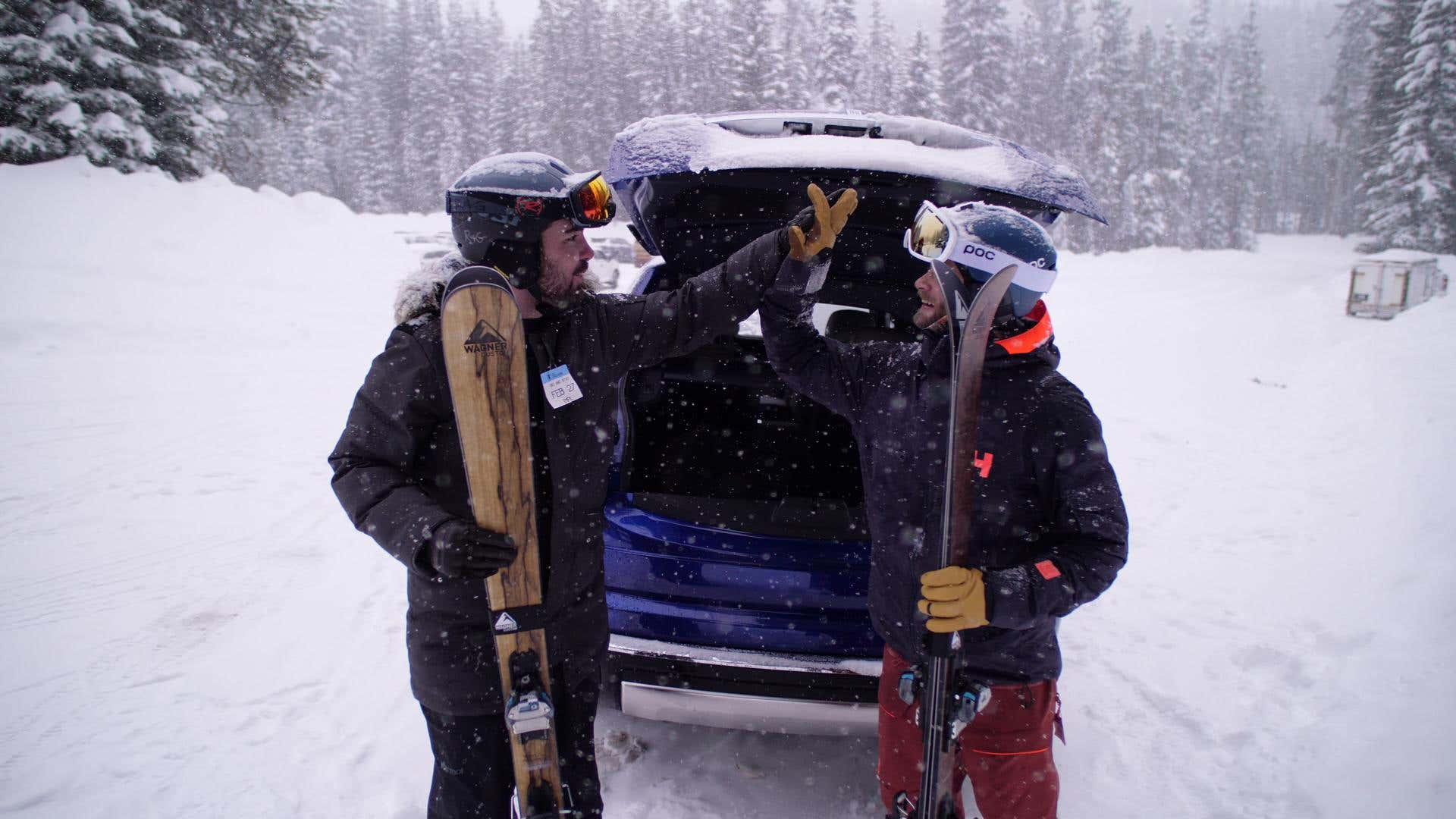 The author hi-fives his friend in front of a Rolls-Royce Cullinan SUV.