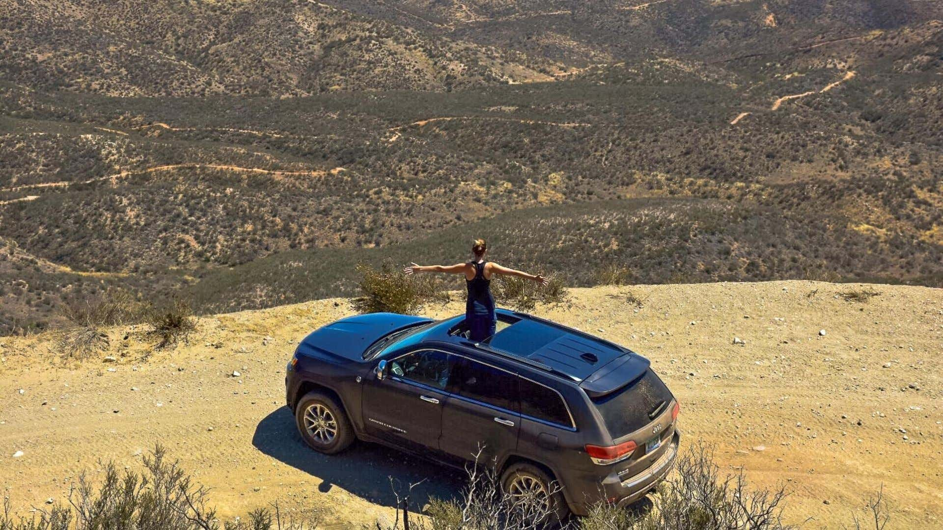 A woman stands out of a 2018 Jeep Grand Cherokee atop a mountain's peak.