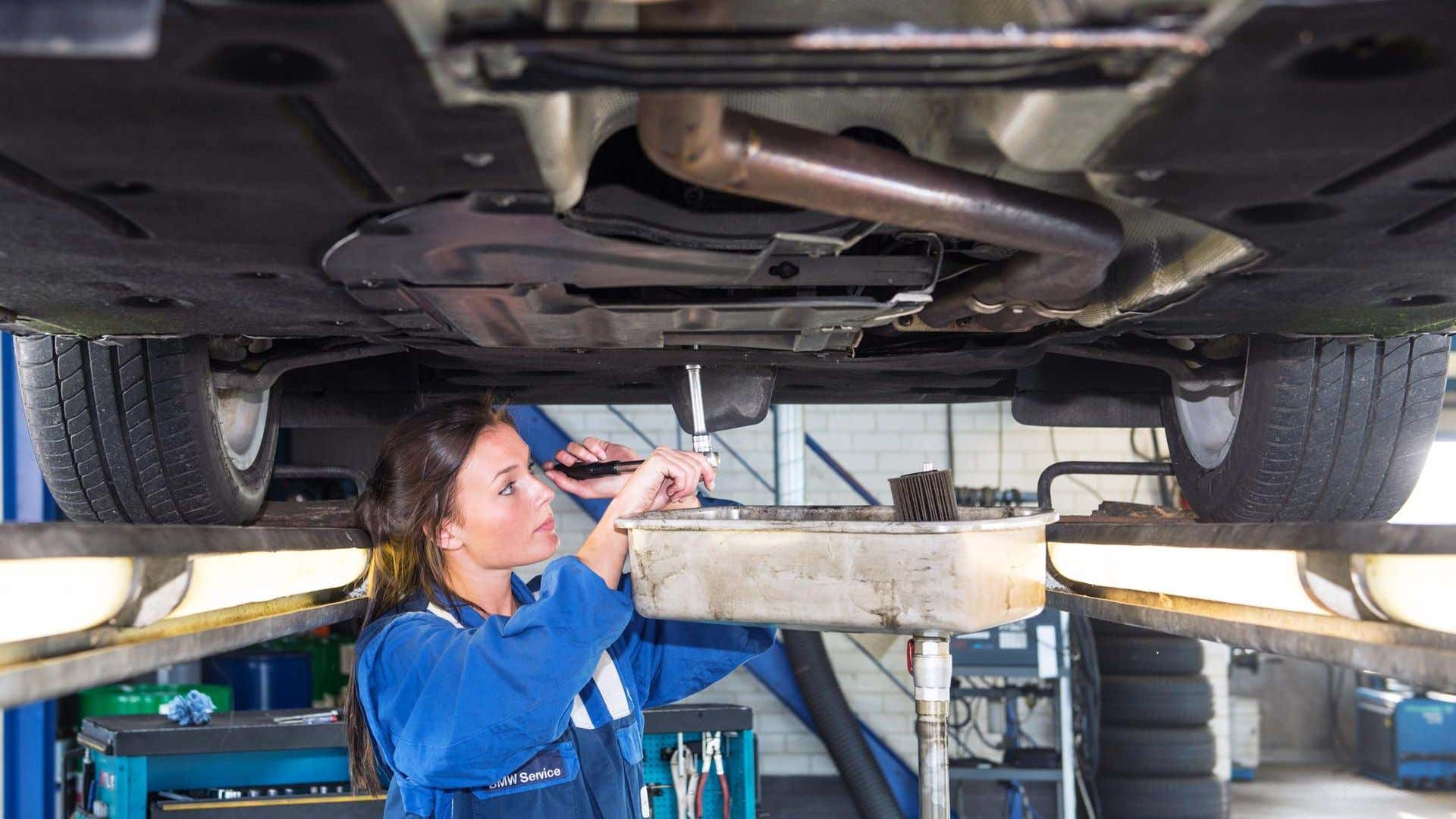 A female mechanic changes a car's oil.