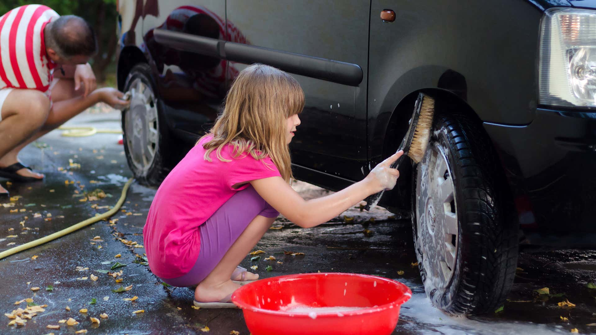 Use a hard-bristle brush to wash a car's tires.