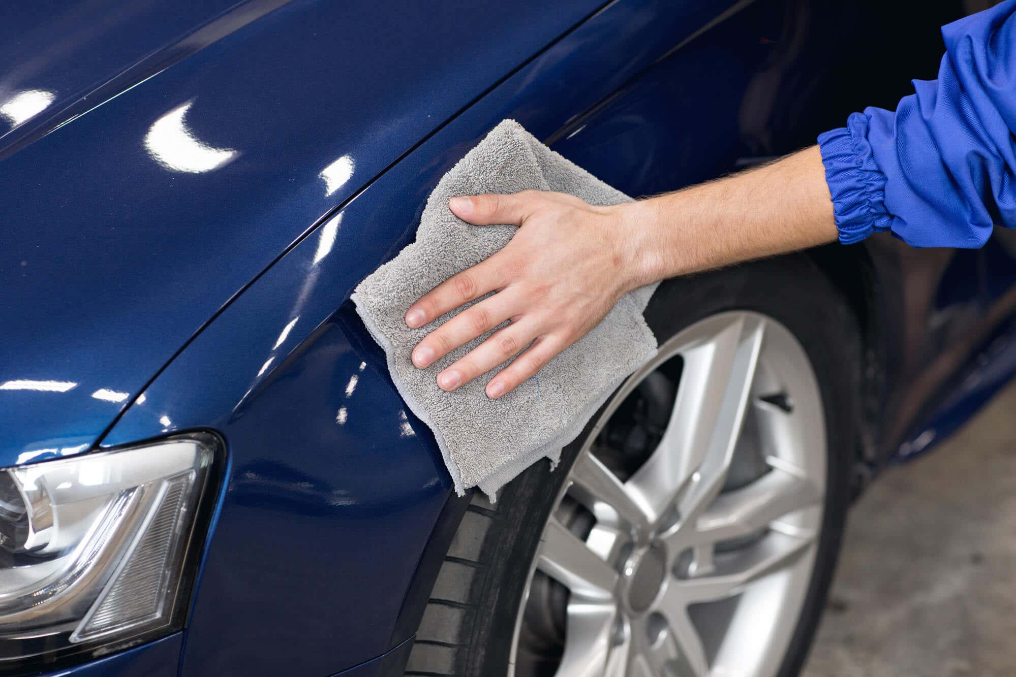 Man polishing cleaning car with microfiber cloth
