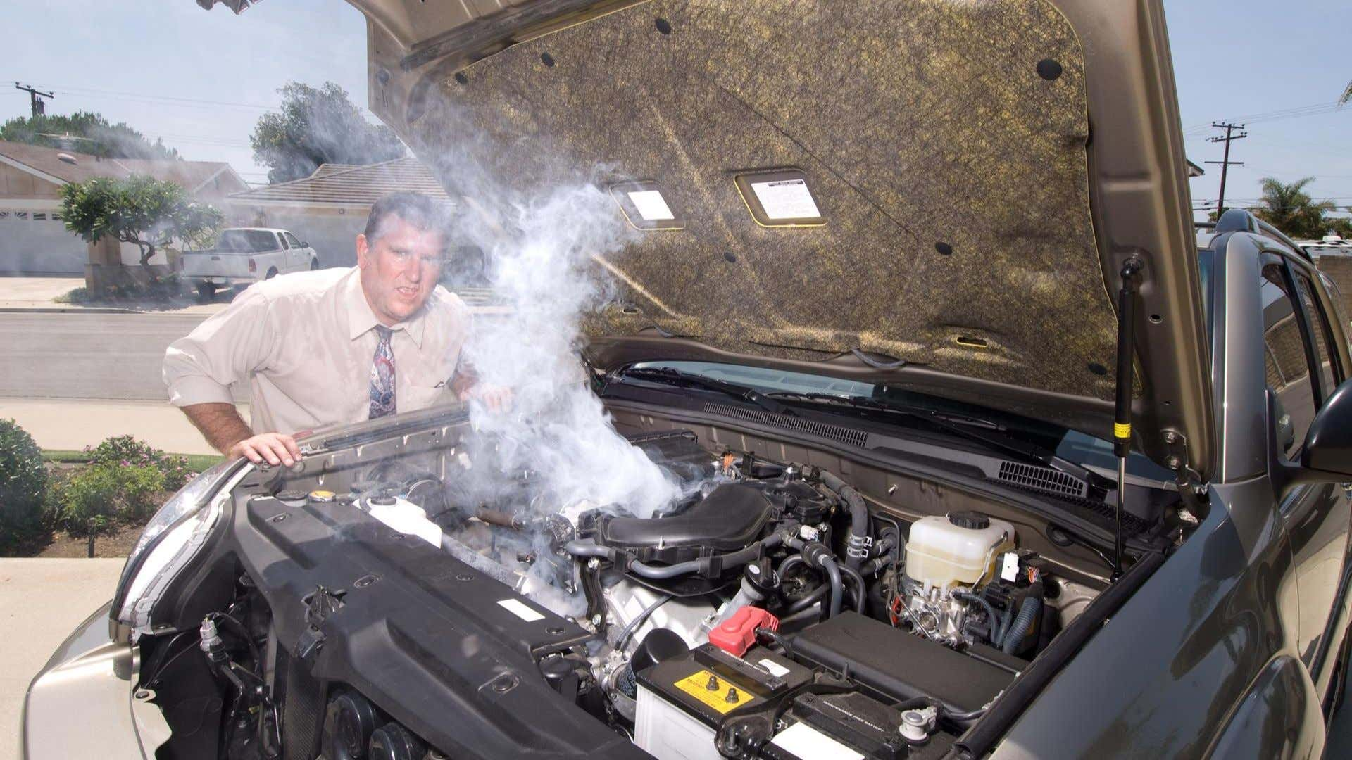 A car's engine smokes as a man looks to camera.