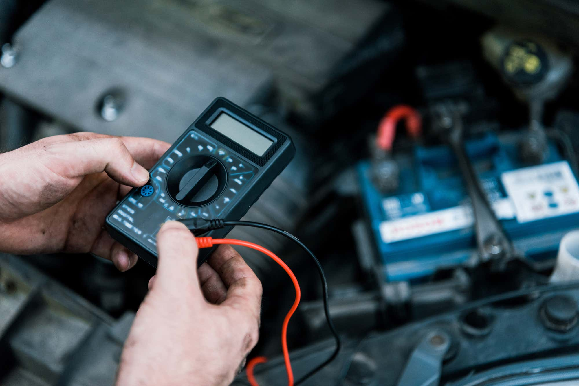 A mechanic testing a battery with a multimeter.