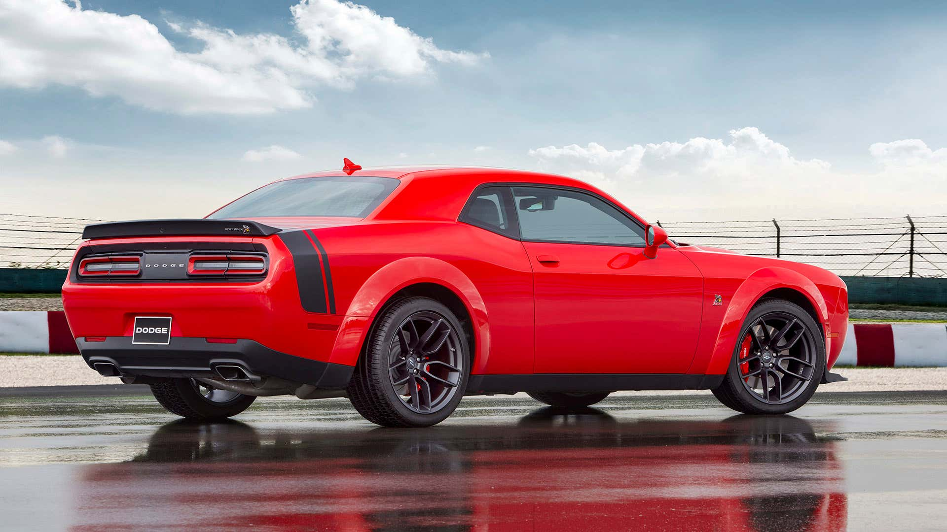 The rear end of a red 2021 Dodge Challenger Scat Pack with.