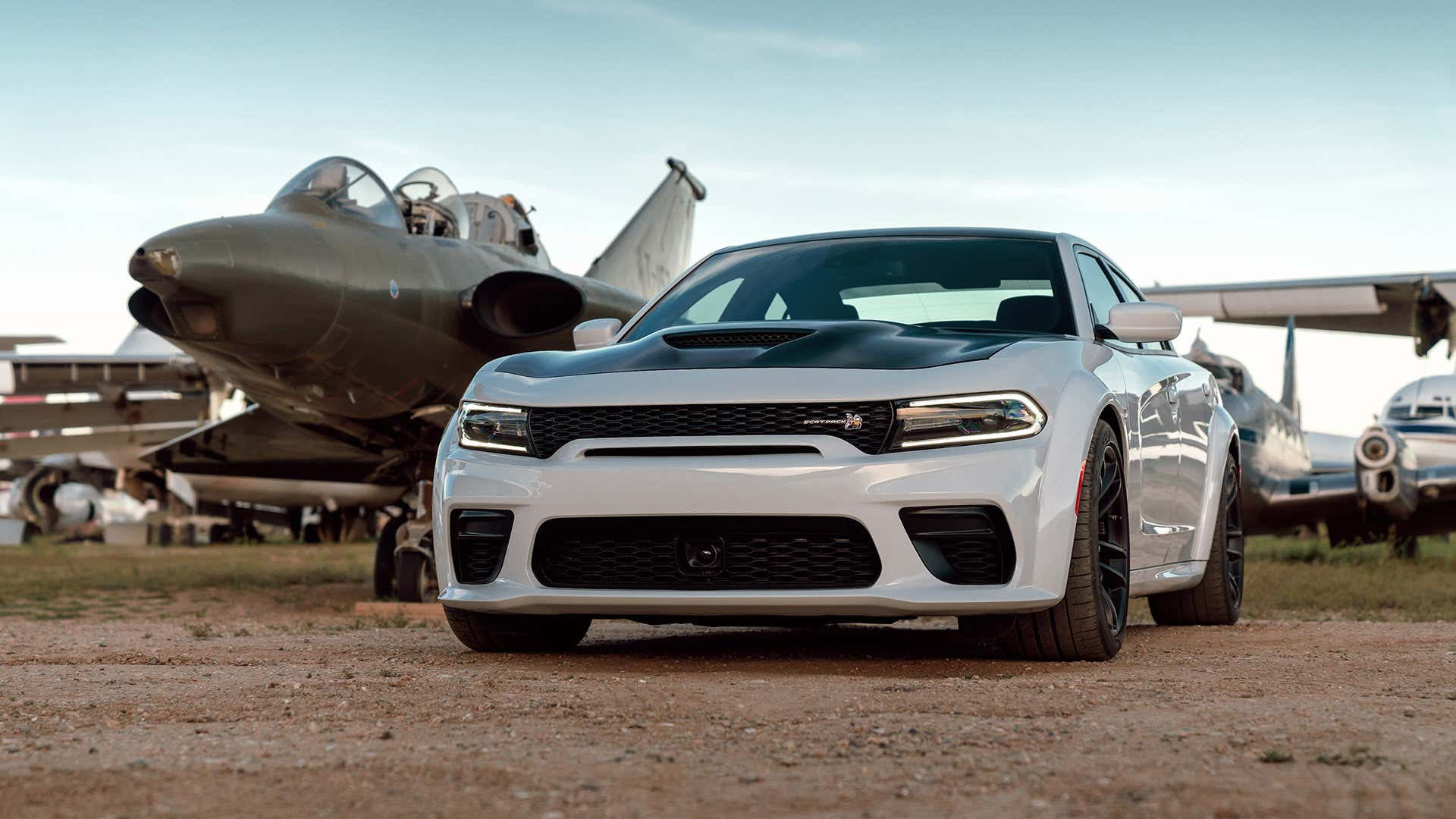 A white 2021 Dodge Charger Widebody Scat Pack rests next to a jet fighter.