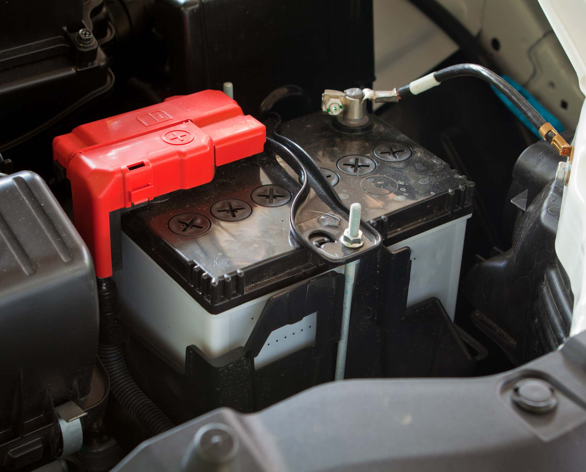 A car battery is shown with a red positive terminal cap.