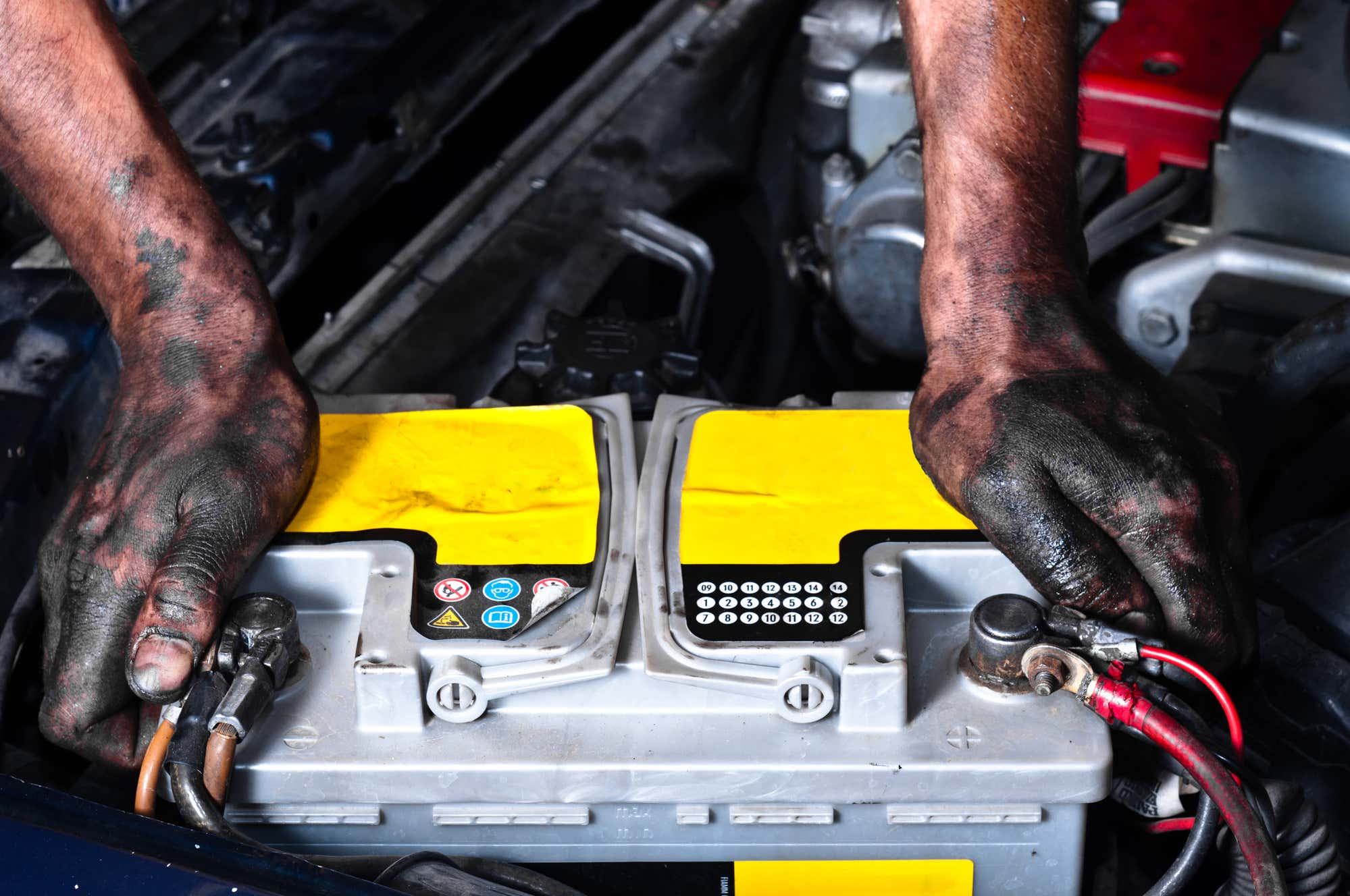 Dirty hands grip a battery in the engine bay.