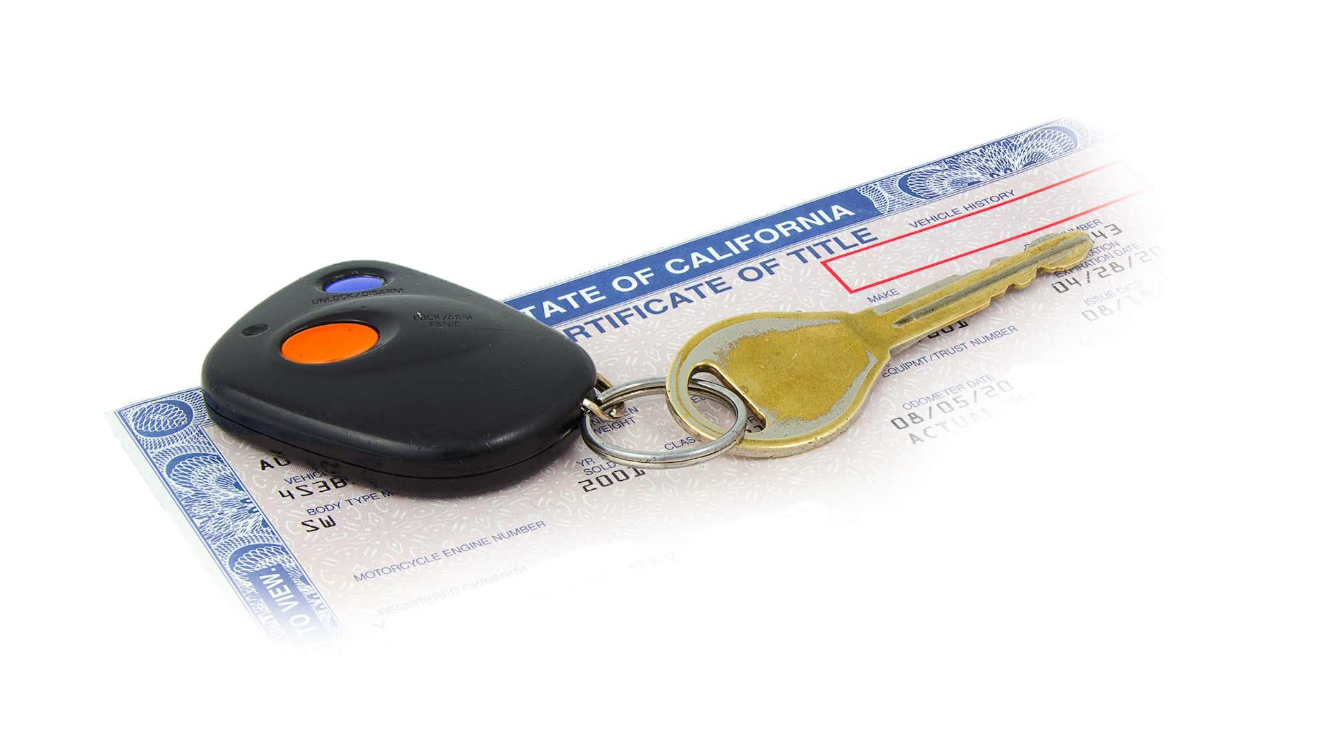 A set of keys sits on a car title.