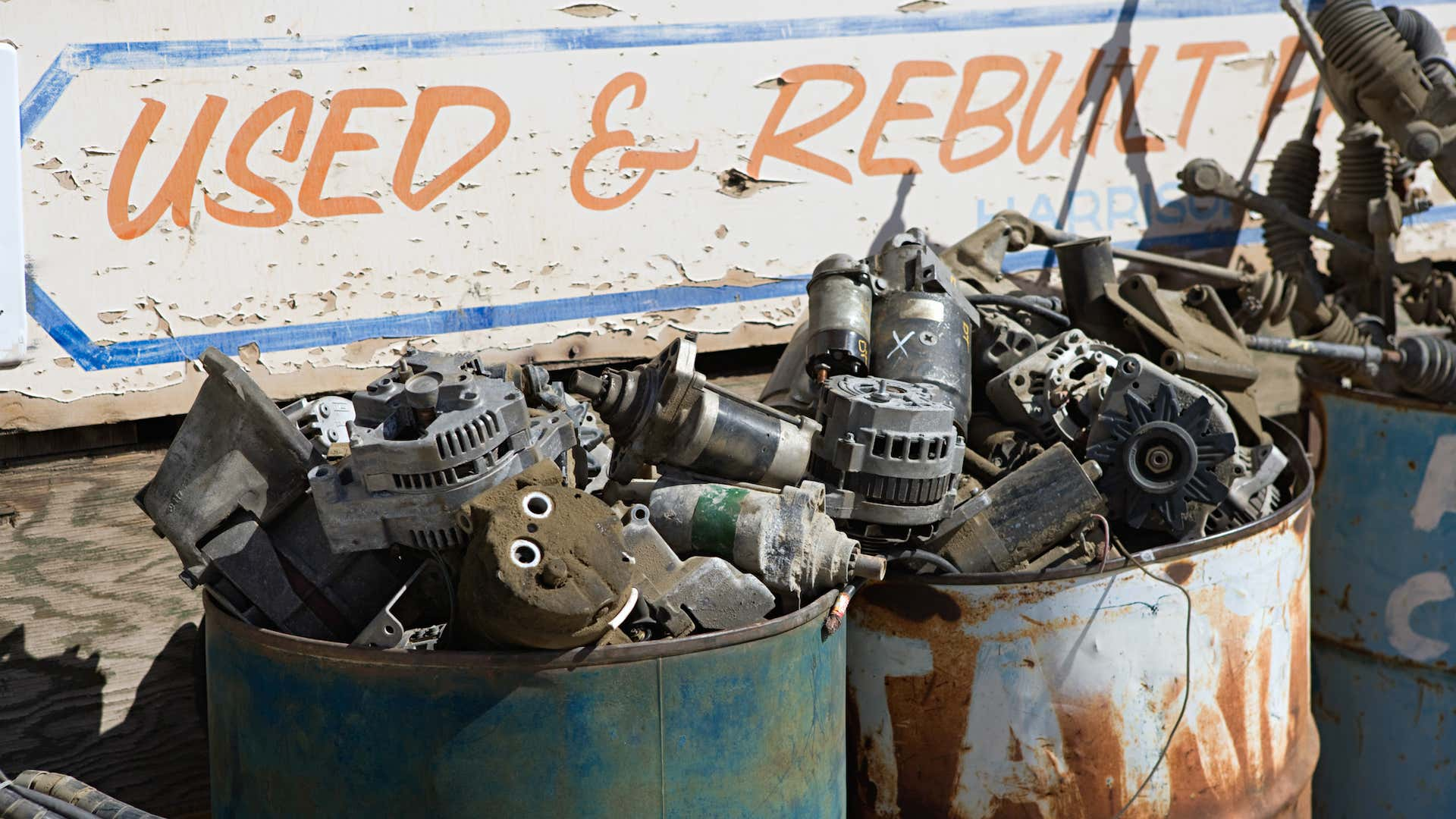 Two metal tanks full of scrapped parts such as alternators and starters.
