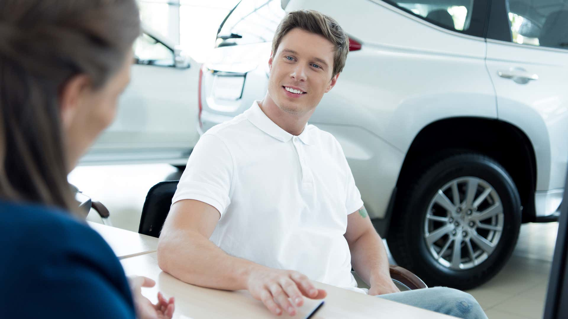 A prospective male buyer in a white polo sits at a car dealership desk.