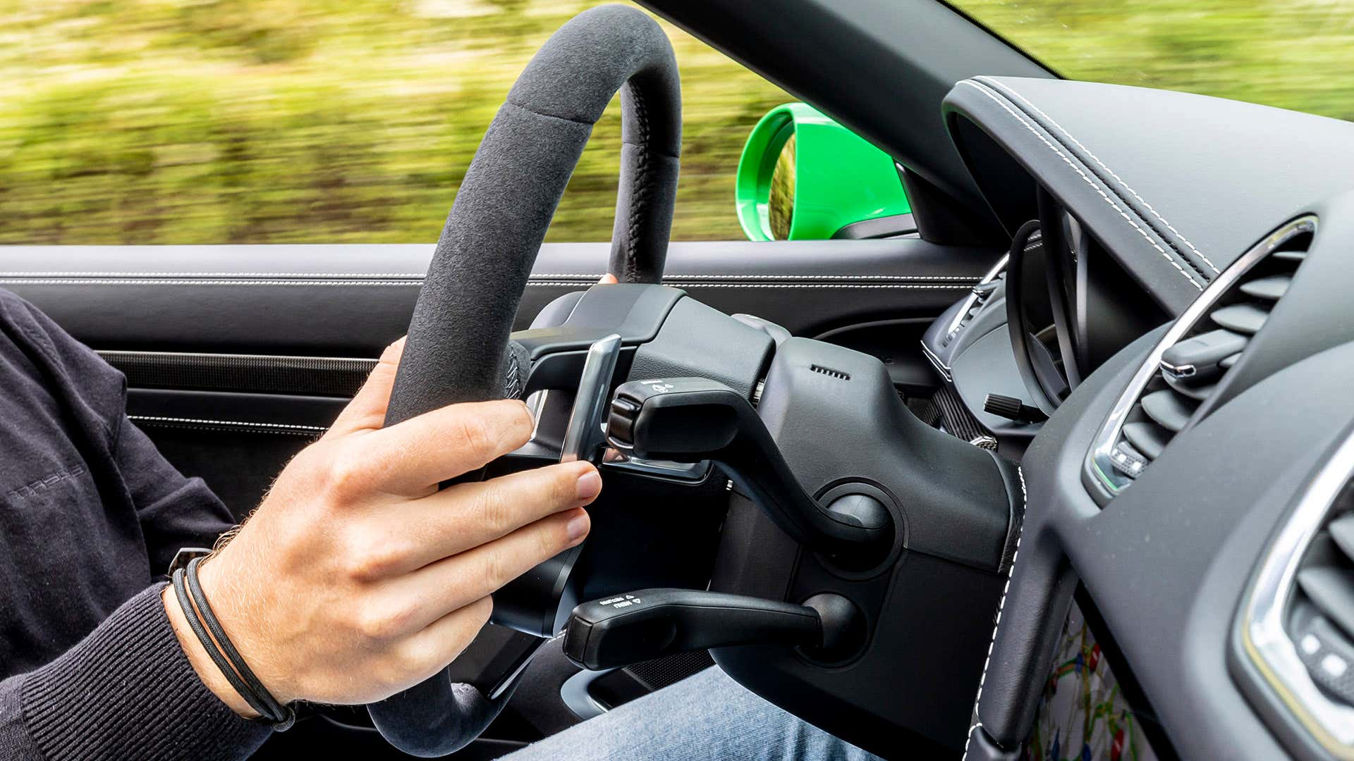 A driver uses the right-hand paddle shifter in a Porsche 911.