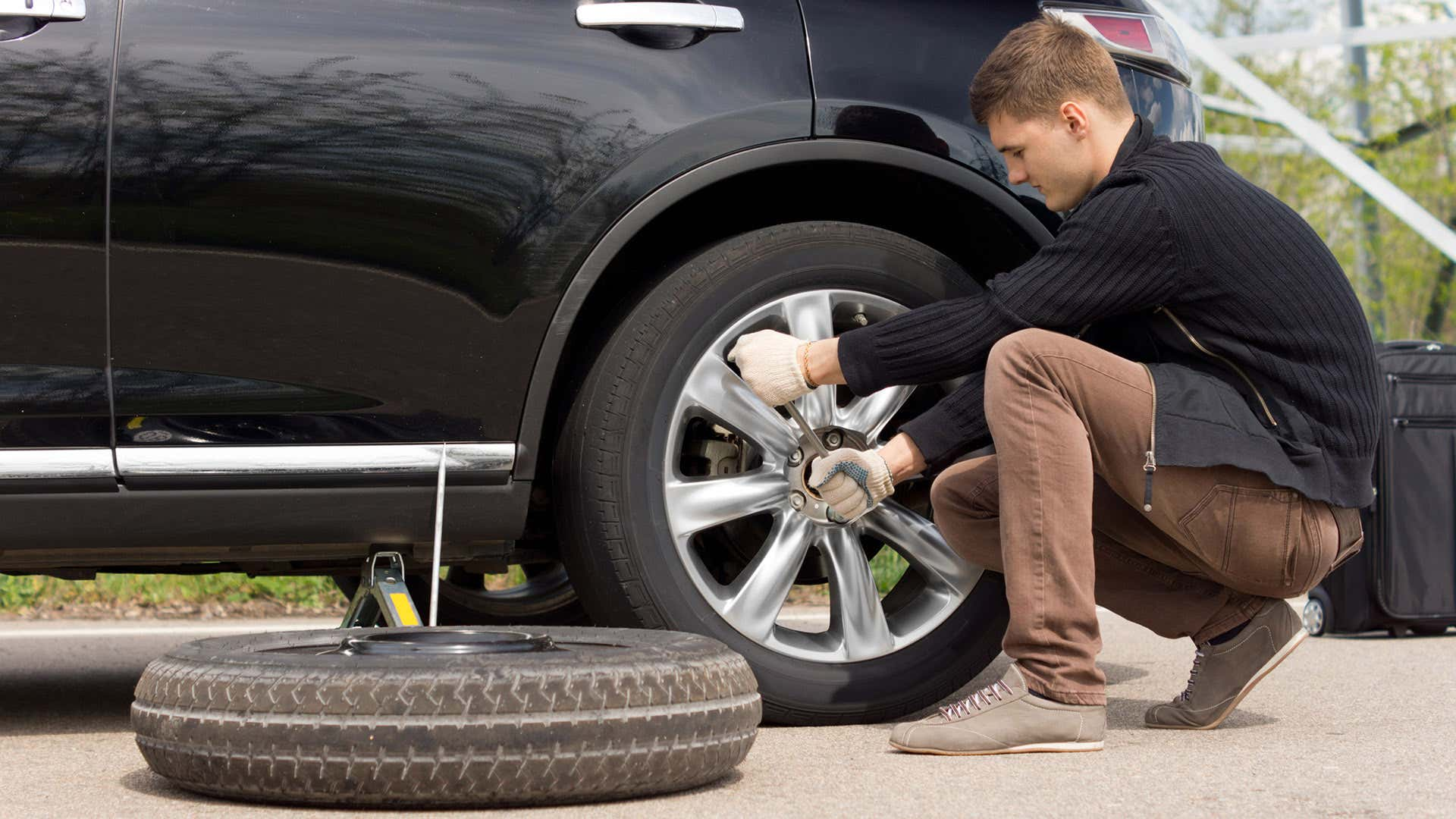 A man wrenches on lug nuts before installing a spare tire.