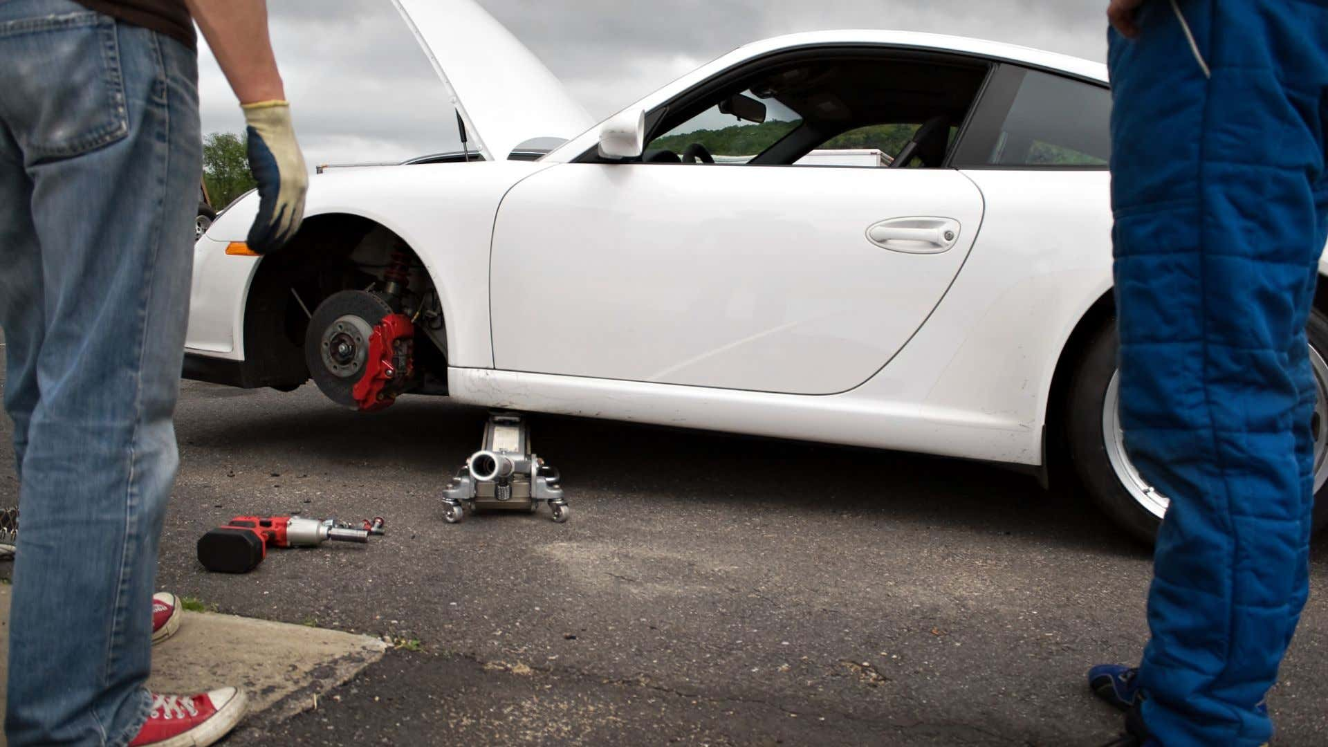 A Porsche's slotted, cross-drilled rotor is exposed.