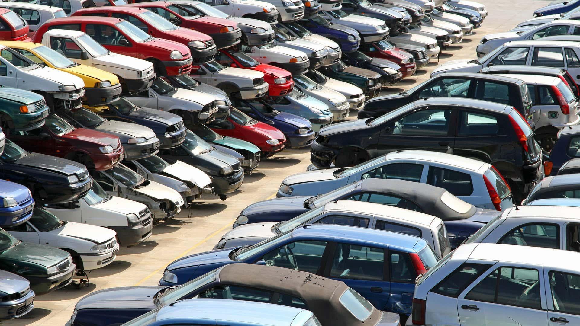 A pool of cars sit in a junkyard.