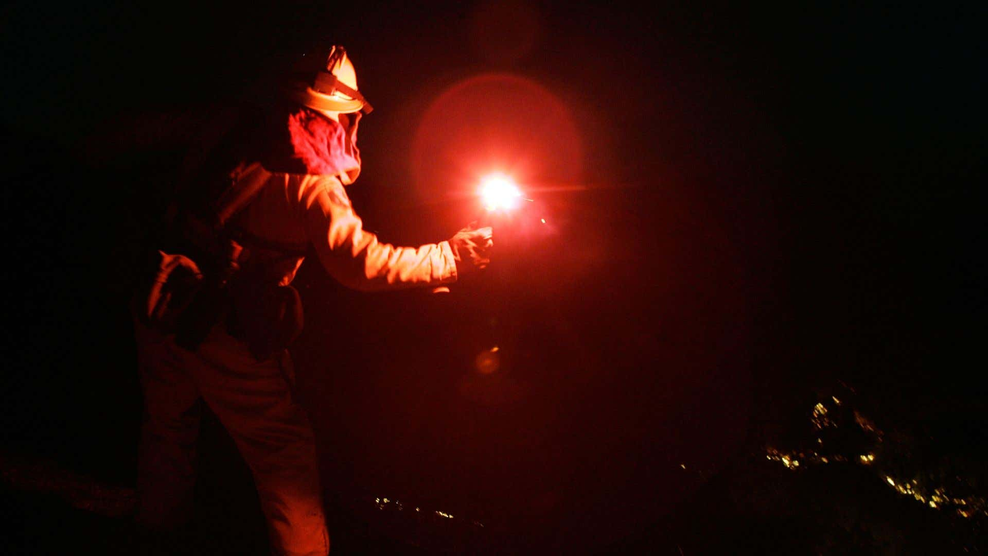 A firefighter throwing a flare.