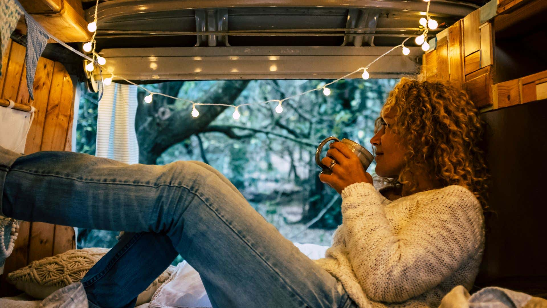 A woman enjoying some coffee in the morning from her van.