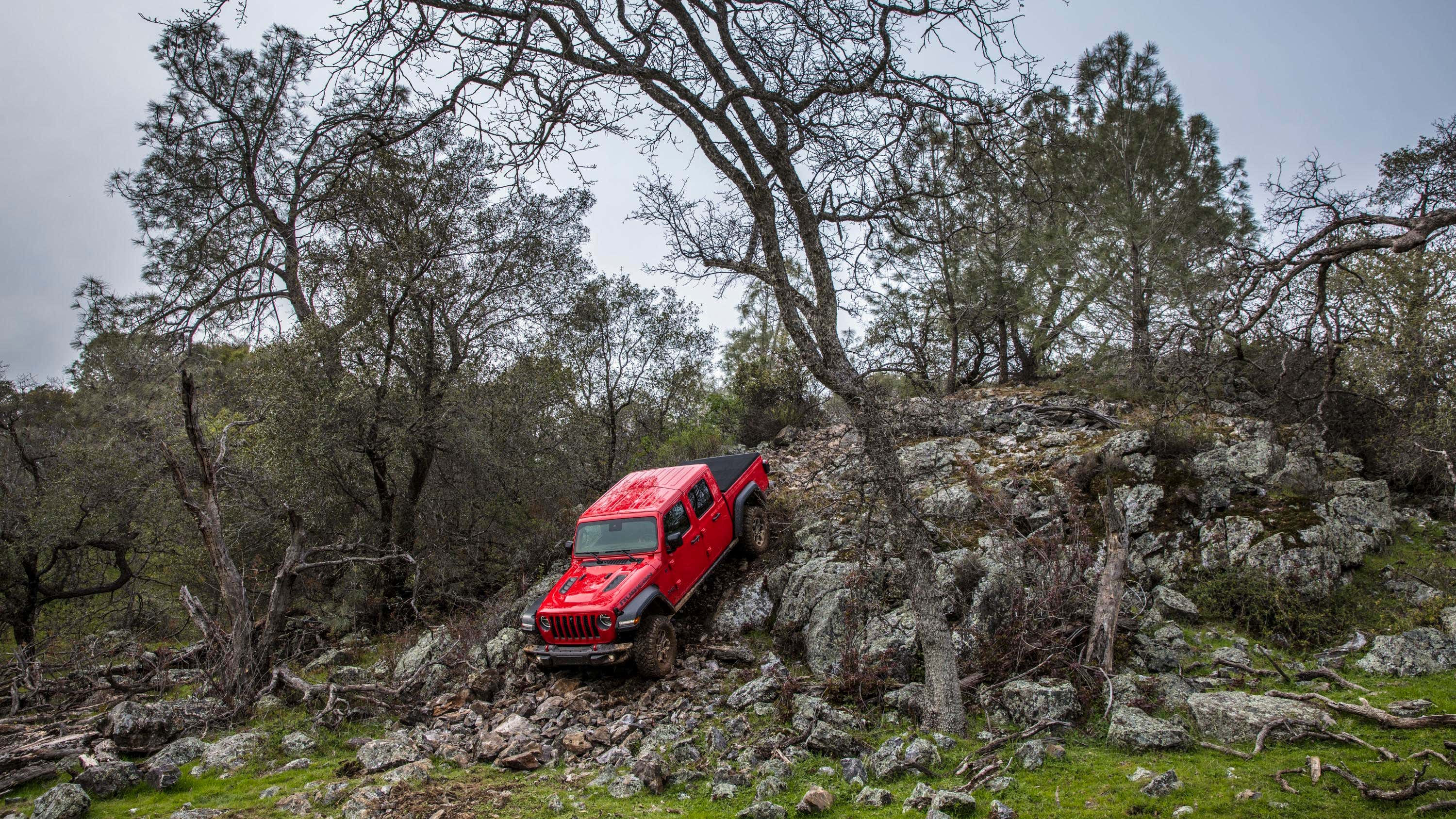A red Jeep Gladiator crawls down a rocky mountain.
