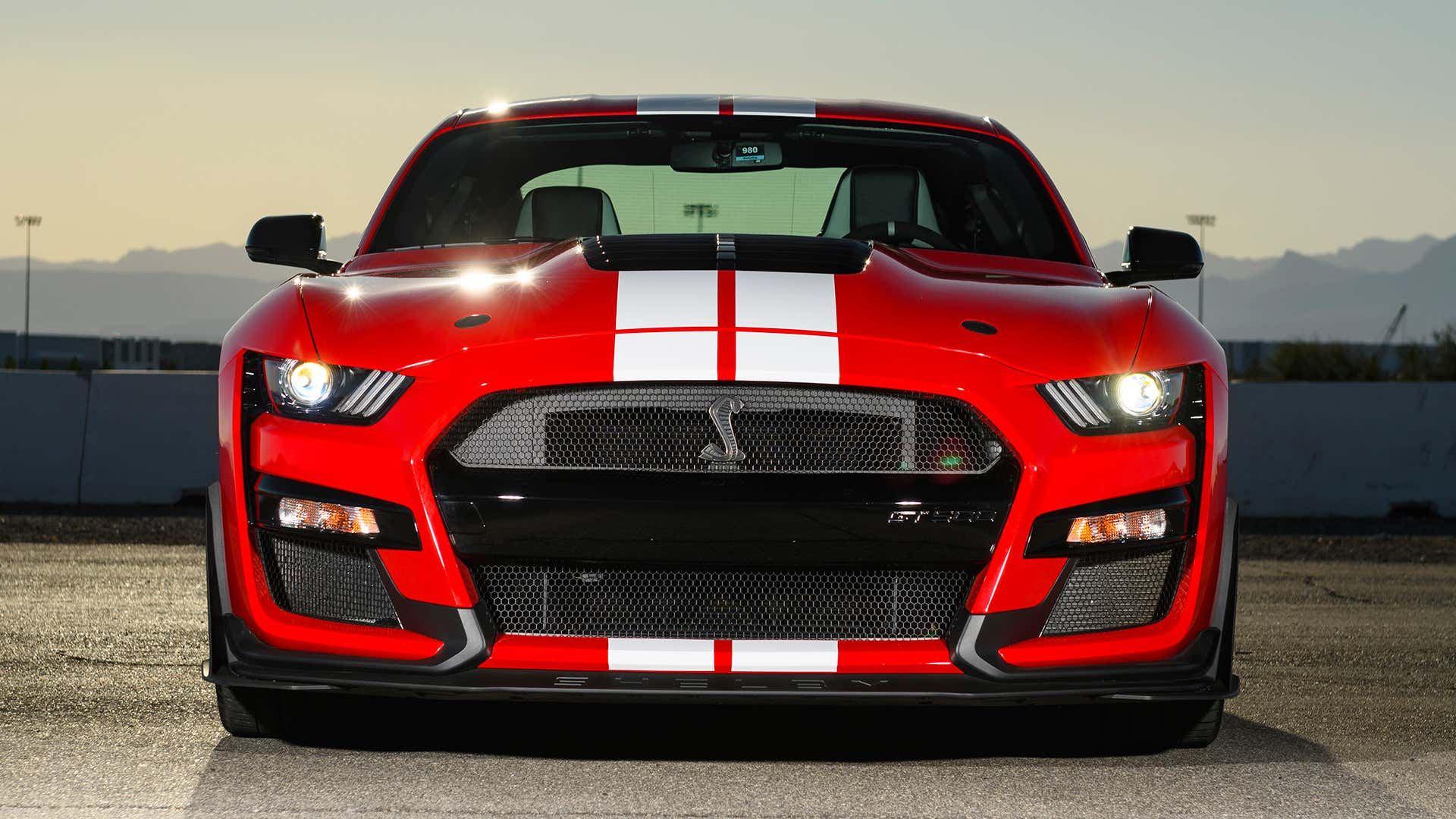 A red Ford Mustang Shelby GT500 faces the camera.