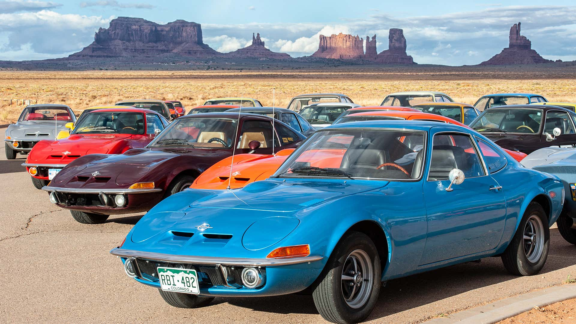 A gathering of colorful Opel GTs in the desert.