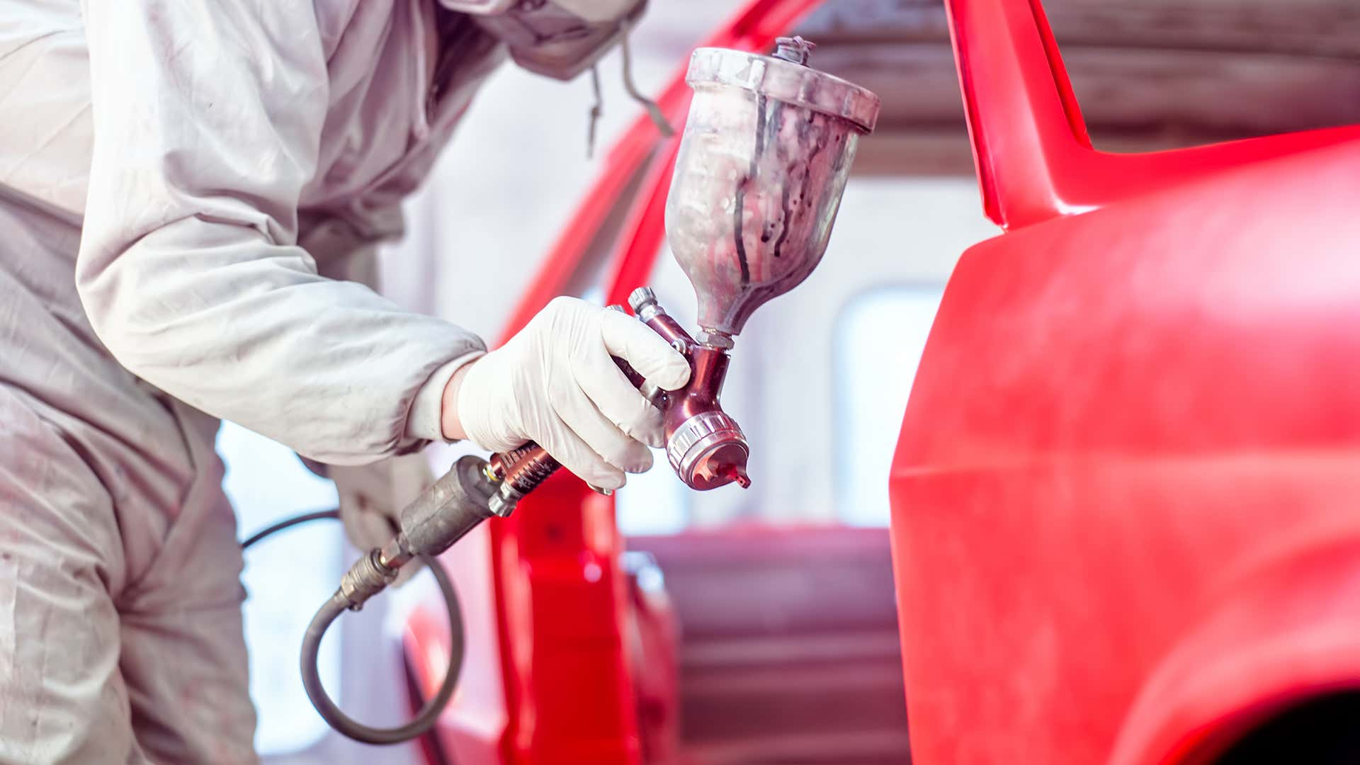 A person uses a pneumatic paint sprayer to paint a car.