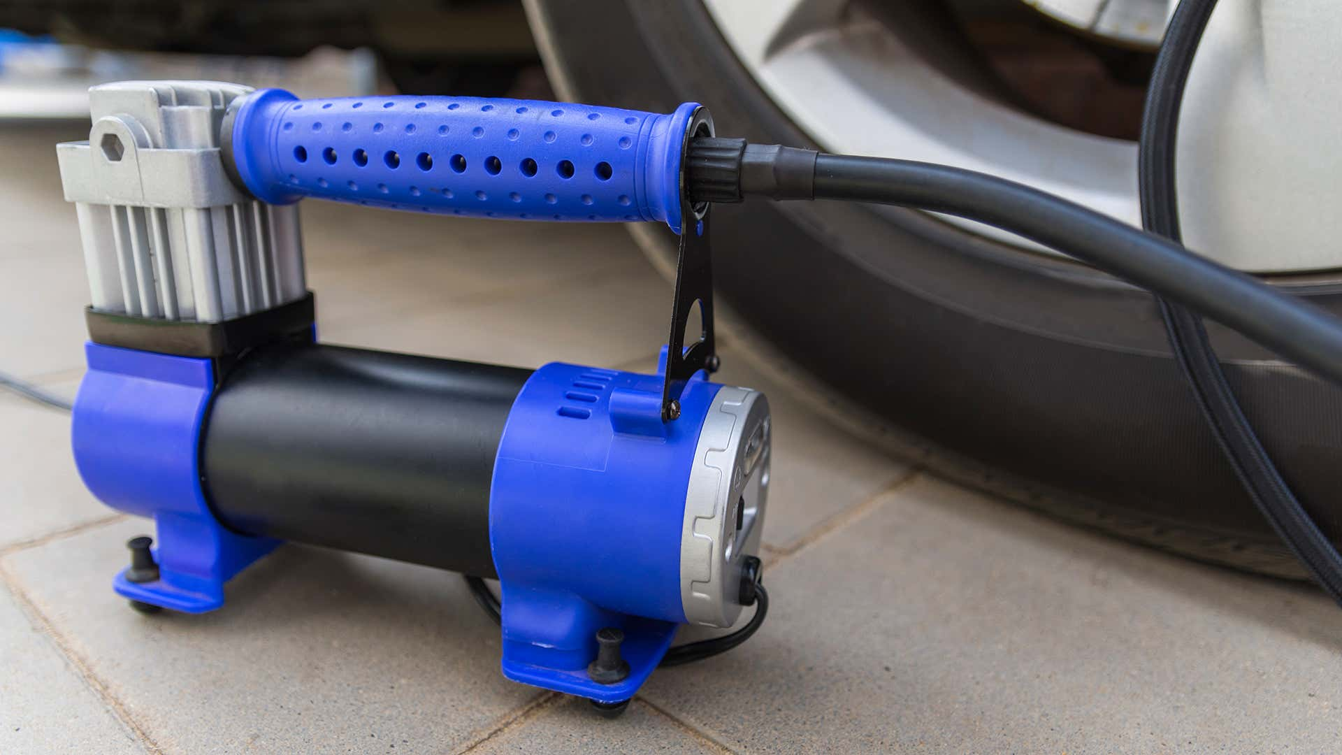 A blue tire inflator next to a wheel.