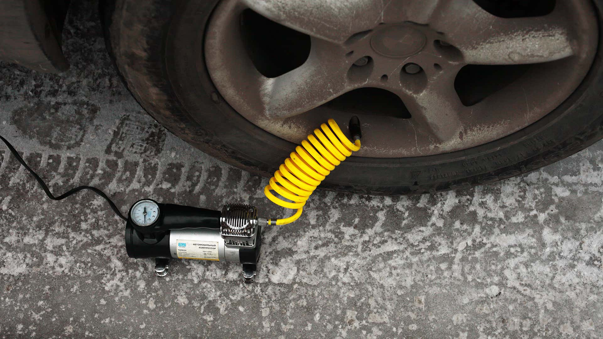A black tire inflator with a yellow coiled hose connected to a BMW wheel and tire.