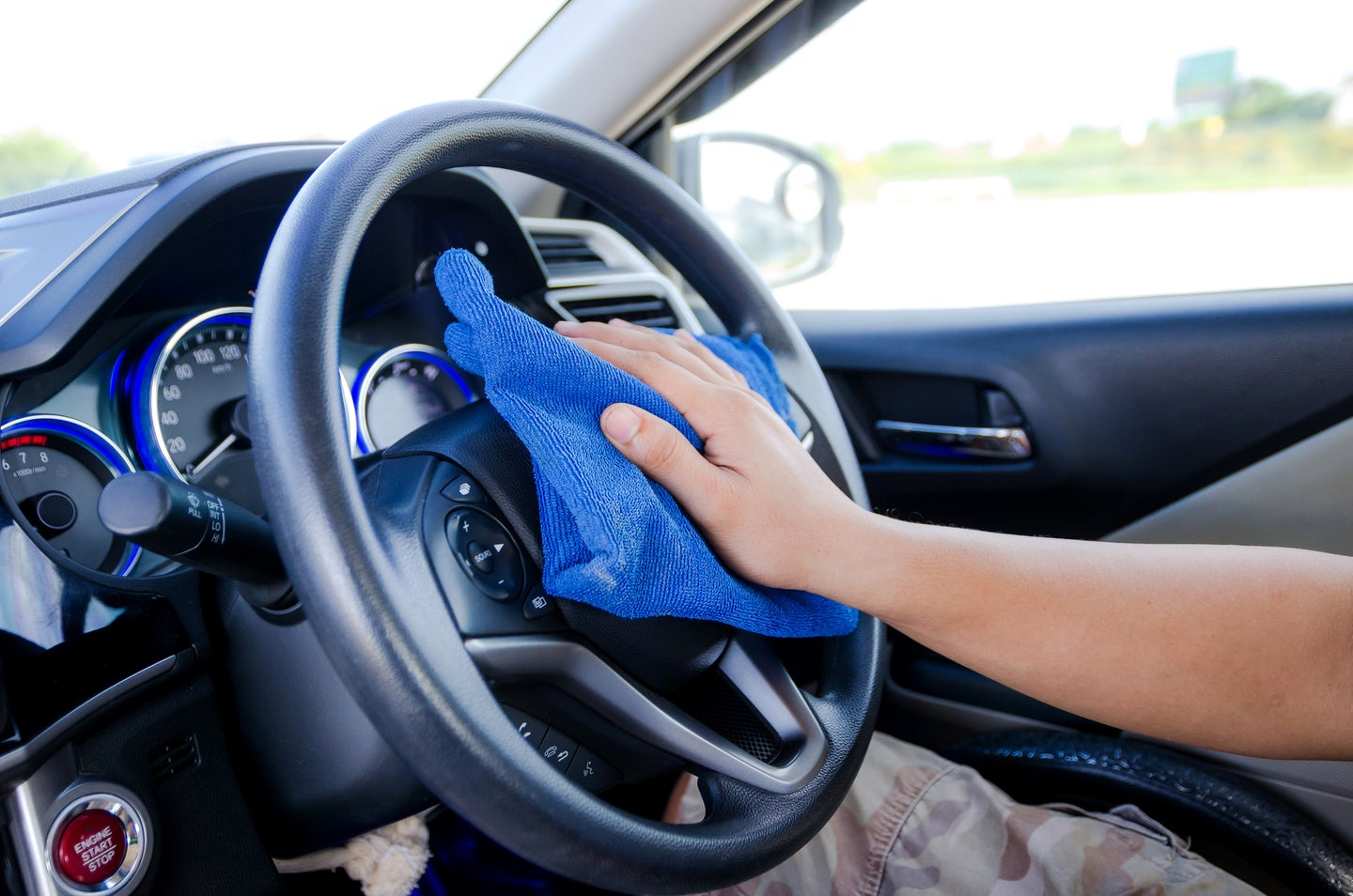 Car steering wheel being cleaned with a wipe.