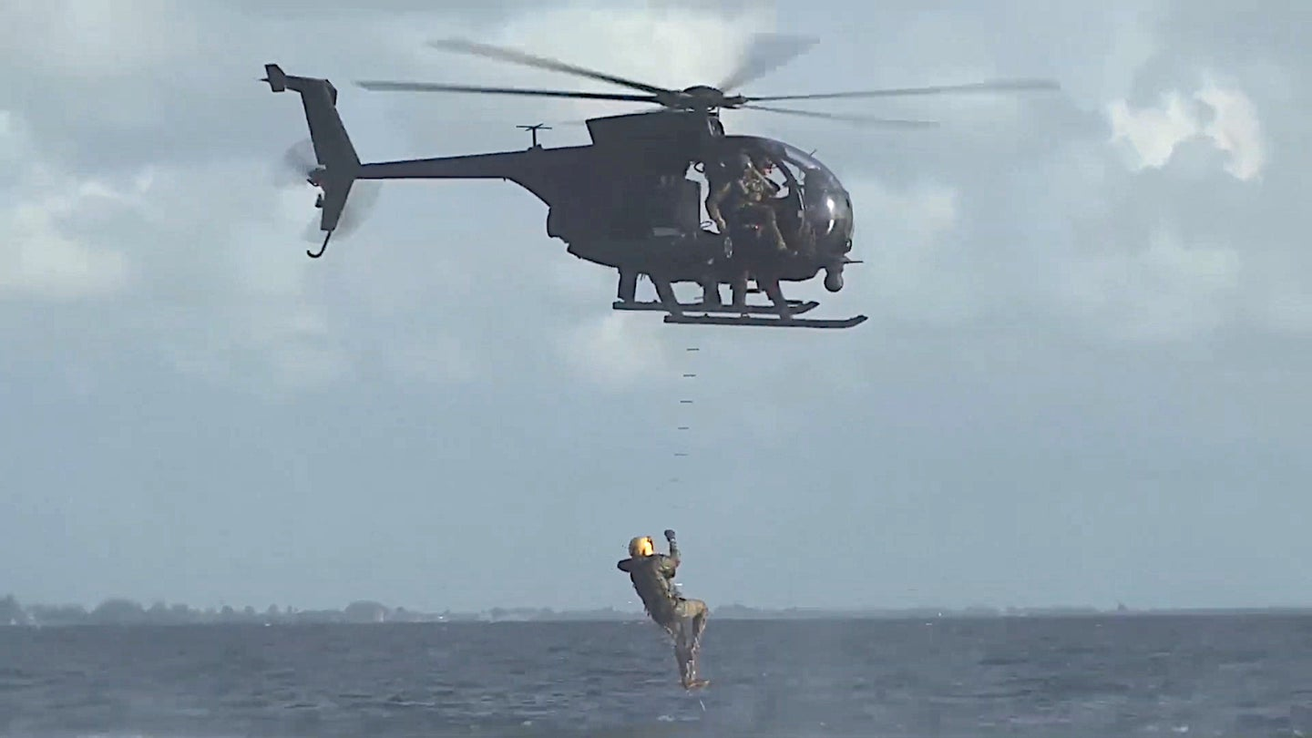 An AH-6 assigned to the US Army's 160th Special Operations Aviation Regiment extracts an individual from the water using a rope ladder.