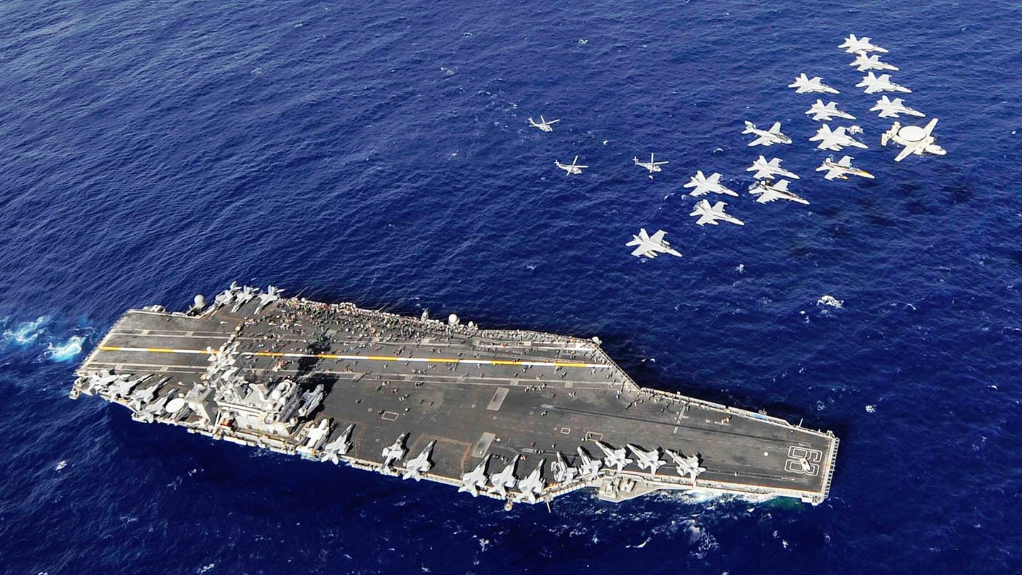 US Navy aircraft fly in formation over the USS Nimitz.