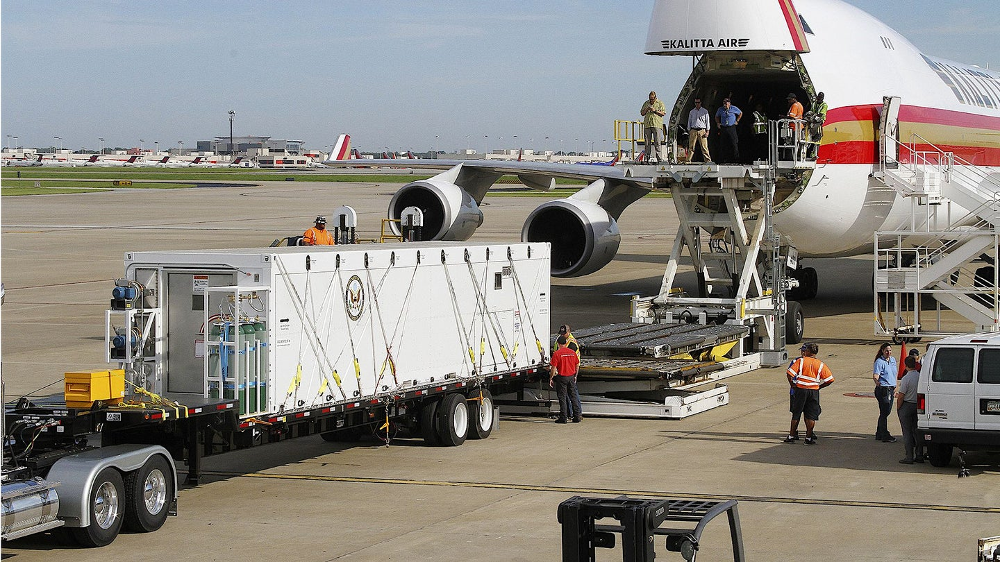 Personnel load a Containerized Bio-Containment System onto a Kalitta Air 747-400ERF.
