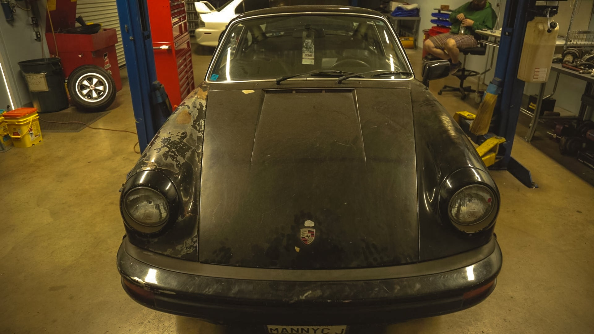 A classic, air-cooled Porsche in a mechanic's bay.