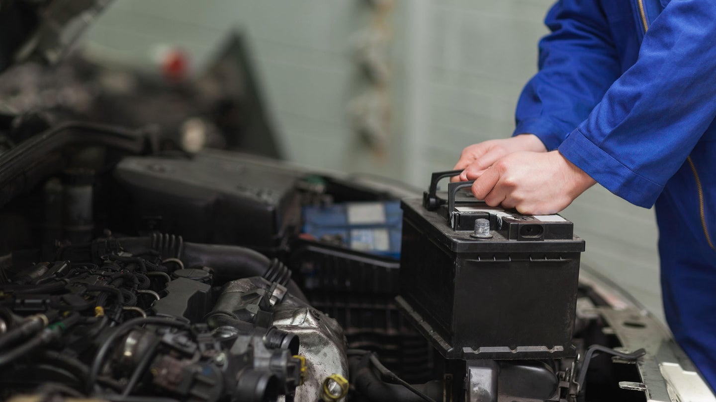 Male mechanic removing and replacing a car battery.