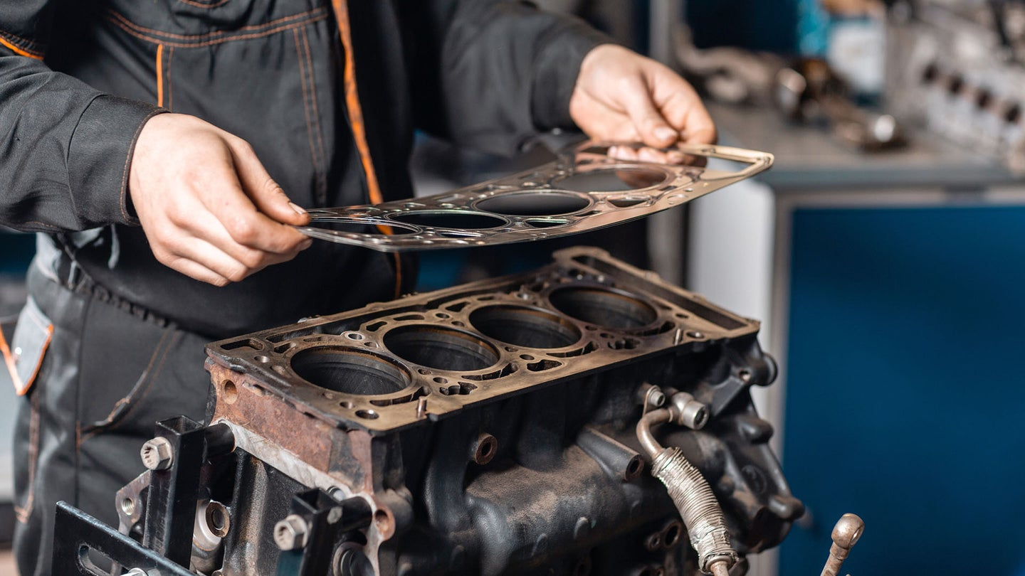 A mechanic applies a new head gasket.