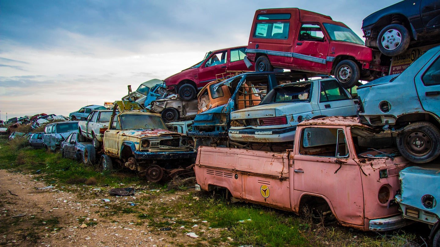 A pile of colorful trashed cars sit in a junkyard.