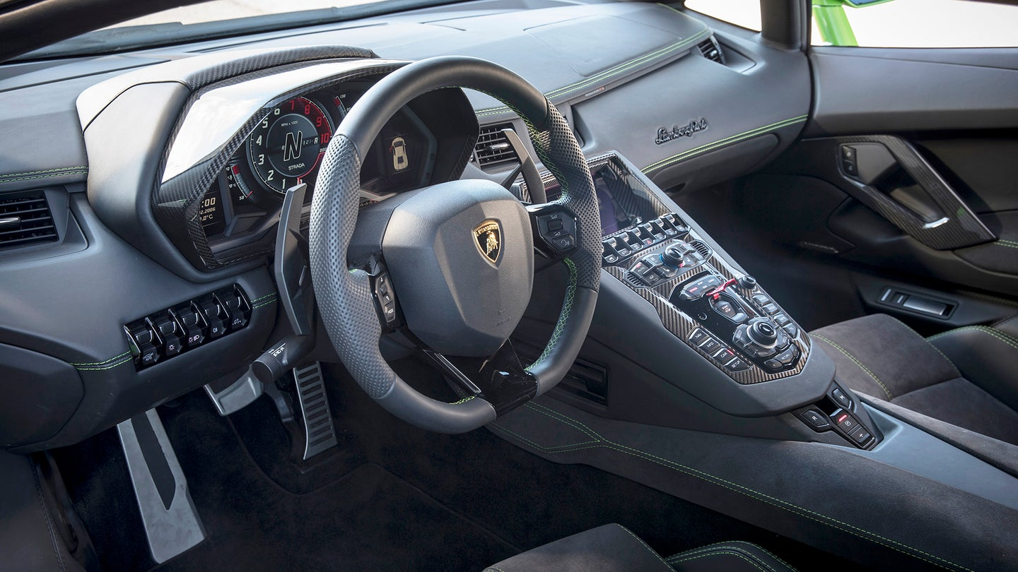 A Lamborghini interior with lots of carbon fiber.