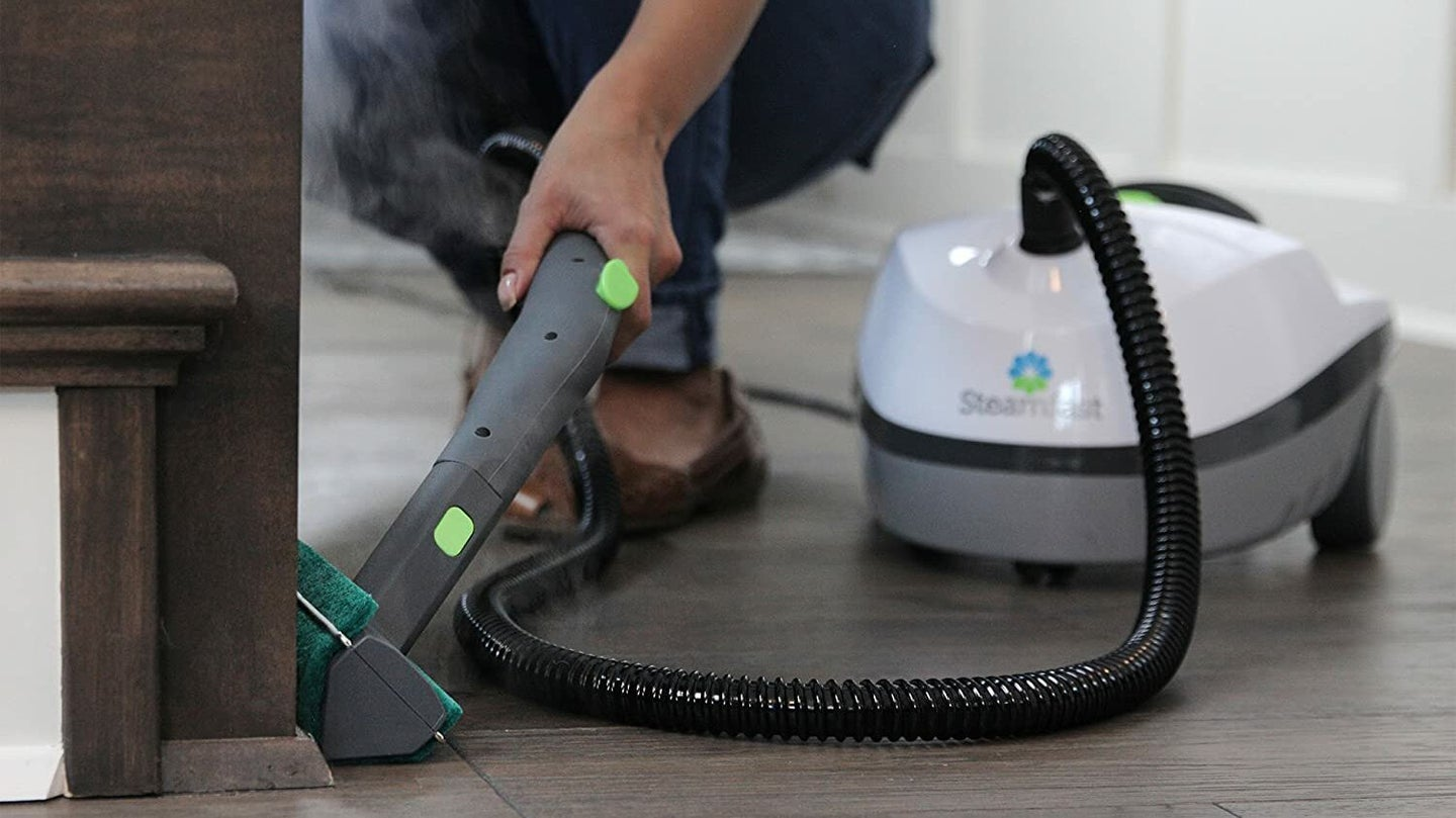 Woman Cleaning With Upholstery Cleaner Machine
