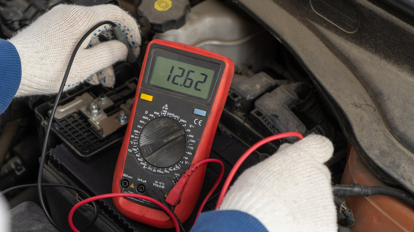 A mechanic using a multimeter to test a car battery.
