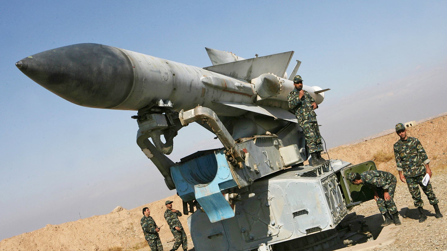 Iranian soldiers stand near a S-200 surf